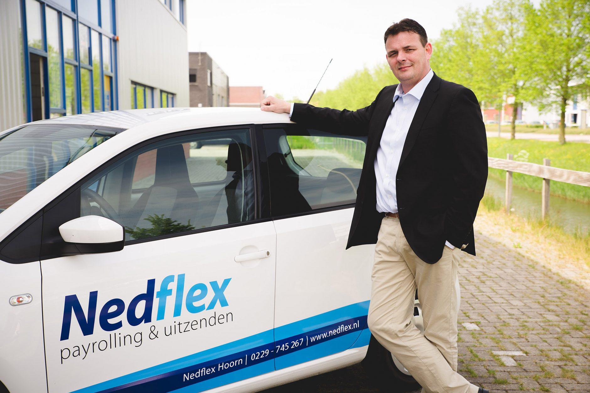 Uitzenden Man leunt tegen auto van Nedflex